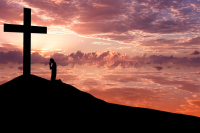 Dramatic sky scenery with a mountain cross and a silhouette of man worshiping to the cross